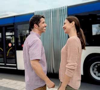 Para zaparatami słuchowymi przed autobusem