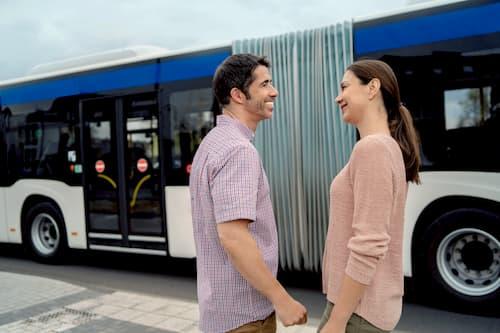 Par med høreapparater foran en bus