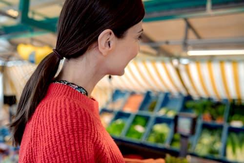 Frau mit Hörgerät auf dem Markt